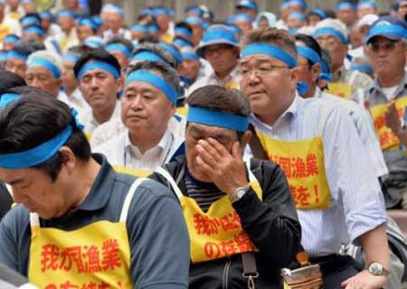 Members of the Japan Fisheries Cooperatives protest against rising fuel prices caused by the weak yen, in Tokyo on May 29, 2013. The weaker currency makes exporters more competitive overseas and inflates repatriated foreign income but has raised the cost of imports.