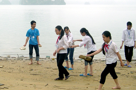 Students collect waste on the beach.