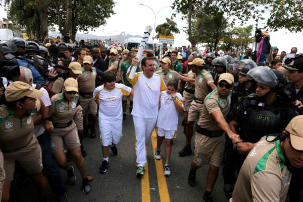 Riot police open way for torch through Rio protest