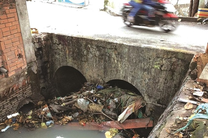 Litter in canals and sewers worsens floods in HCM City